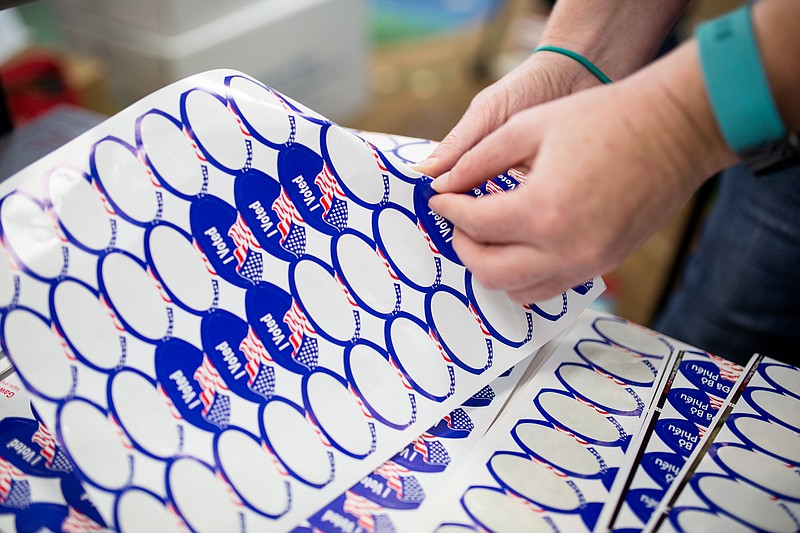 A poll worker at the North Park Library is shown handing out stickers to vote...