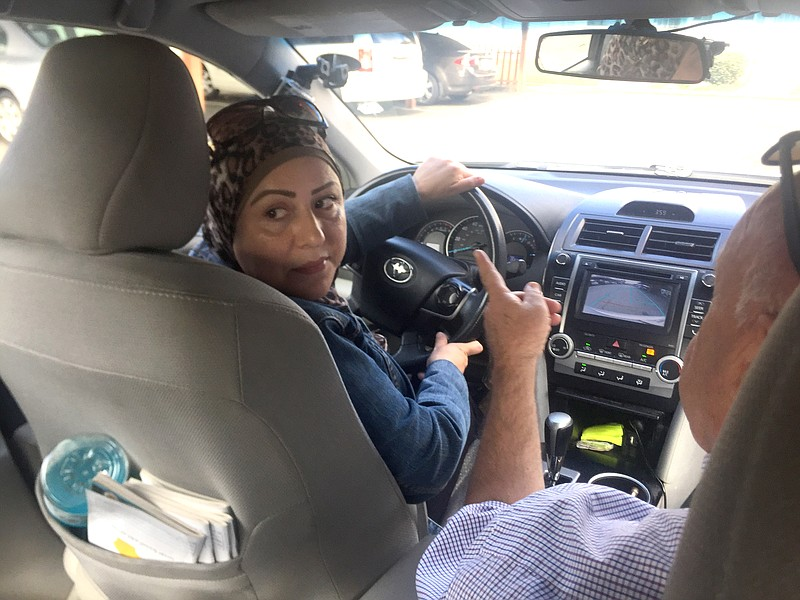 Abir Aldabbagh turns to look out her back window as she reverses her car duri...