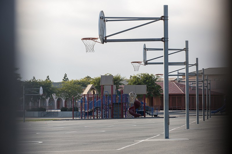 An empty playground is shown through a fence at Ocean View Hills Elementary i...