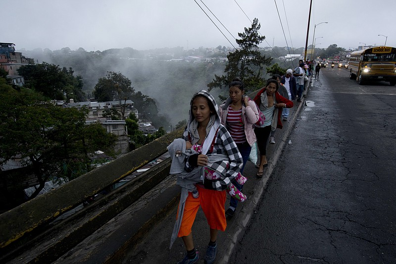 Honduran migrants leave Guatemala City at sunrise as they make continue their...