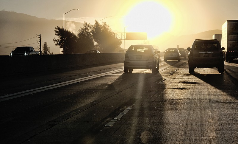 Photo morning commuters drive into downtown Los Angeles as the sun rises alon...