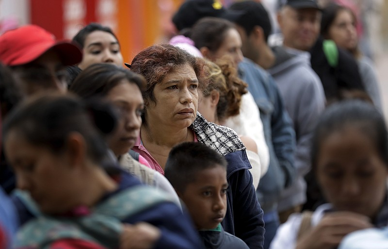 People seeking asylum in the United States line up to receive a number at the...
