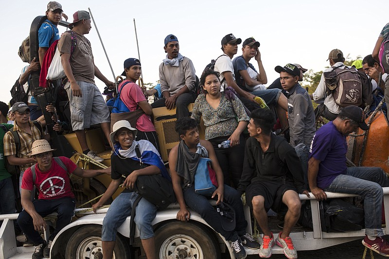Central American migrants traveling with a caravan to the U.S. crowd onto a t...