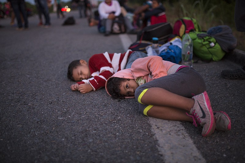 Children wait for a ride on the side of the road, as a caravan of Central Ame...