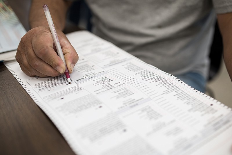 A voter in City Heights fills out a ballot at the City Heights/Weingart Libra...