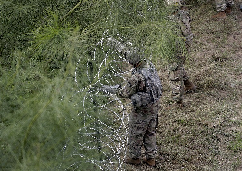 Members of the U.S.military place razor wire along the U.S.-Mexico border nea...