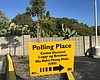 A polling place sign is shown in a parking lot ...