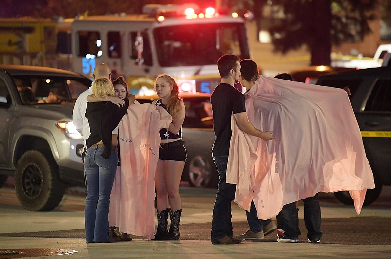 People comfort each other as they stand near the scene Thursday, Nov. 8, 2018...