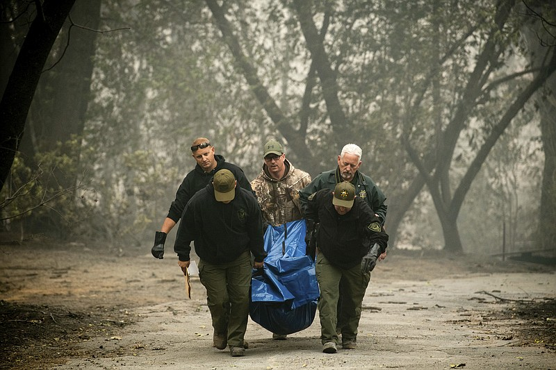 Sheriff's deputies recover the remains of a victim of the Camp Fire on Saturd...