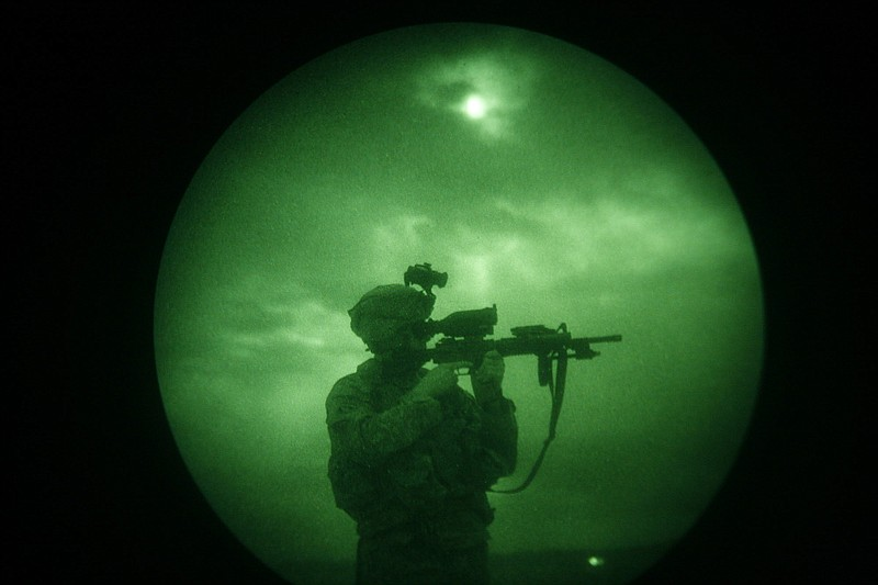A U.S soldier looks through the scope of his weapon during a night patrol in ...