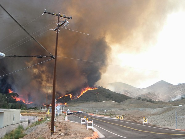 Smoke and flames creep down a hillside behind Harmony Gro...