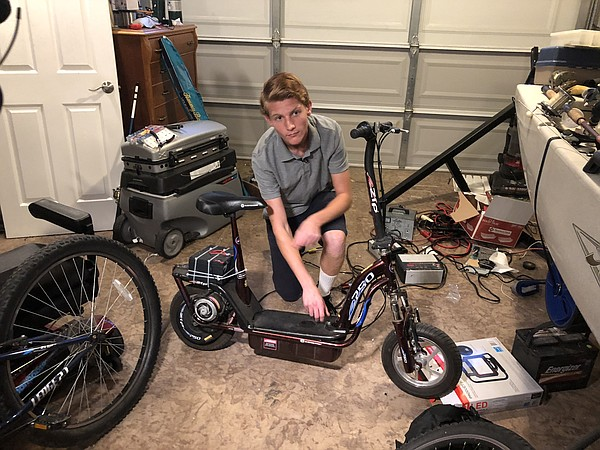 Brokton Harris shows batteries that he added to his scoot...