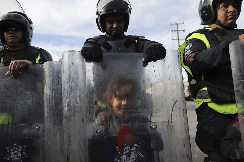 A migrant child plays behind the shield of Mexican police officer in riot gea...