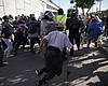 Migrants break past a line of police as they ru...