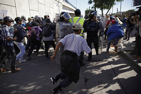 Migrants break past a line of police as they run toward t...