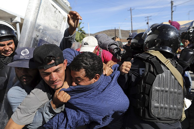Migrants clash with Mexican police at the Mexico-U.S. border after getting pa...
