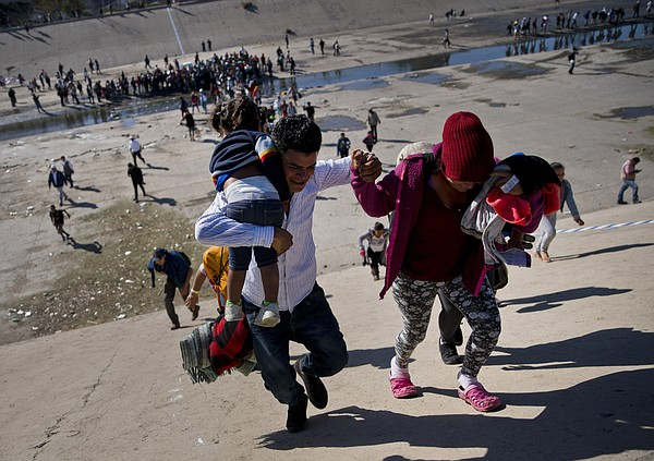 Migrants walk up a riverbank at the Mexico-U.S. border af...