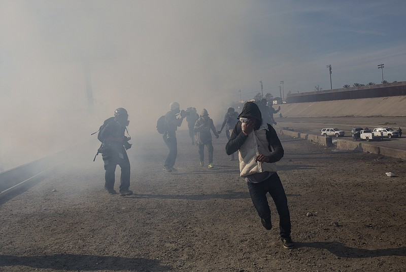 Migrants run from tear gas launched by U.S. agents, amid photojournalists cov...