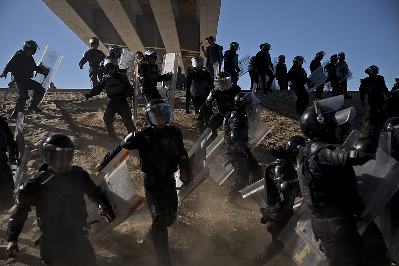 Mexican police run as they try to keep migrants from getting past the Chaparr...