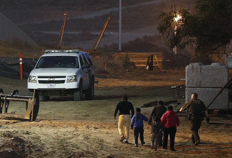 Migrants are escorted by a U.S. Border Patrol agent as they are detained afte...