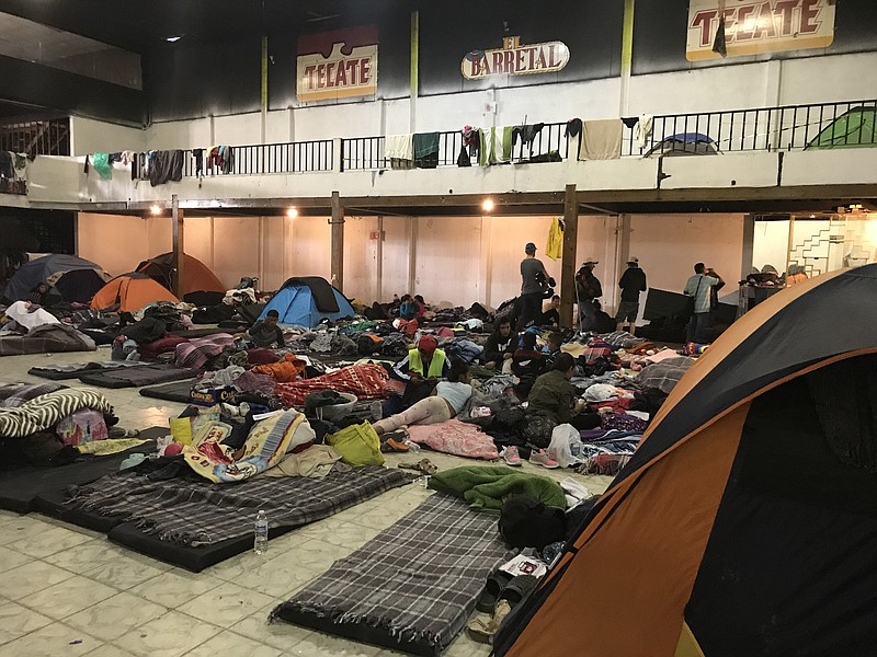 Migrants arrange cots on a floor at El Barretal, Dec. 4, 2018.