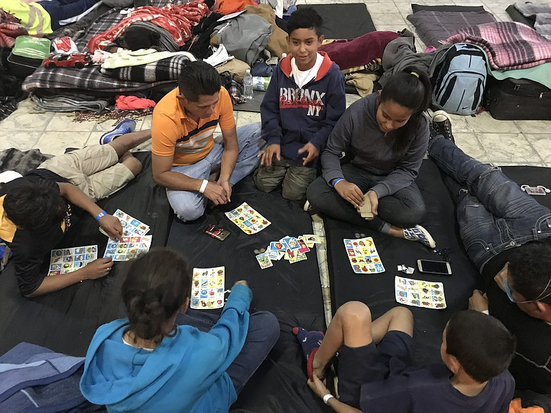 Migrants play Loteria (mexican bingo) at El Barretal, Dec. 4, 2018.