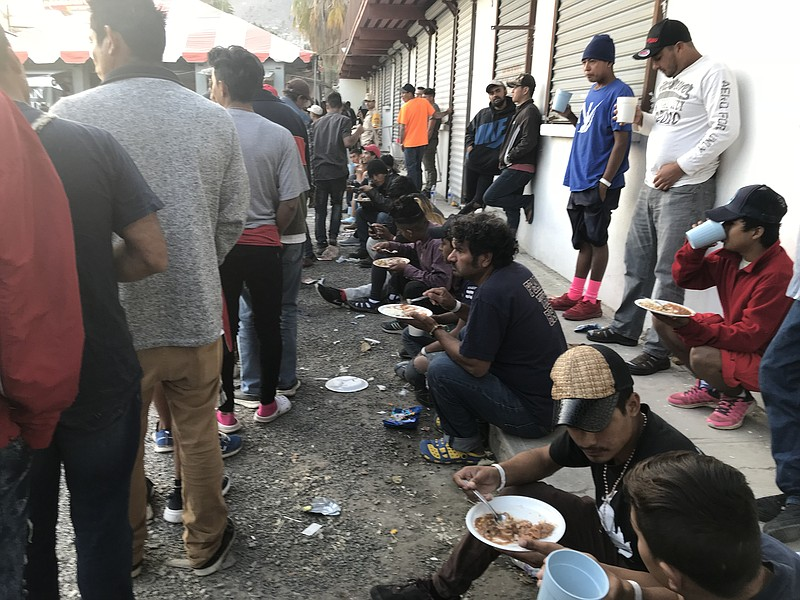 Migrants eat at El Barretal, Dec. 4, 2018.