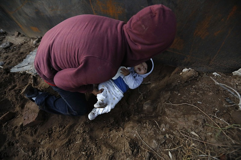 A Honduran migrant passes his eight-month-old son through a hole under the U....