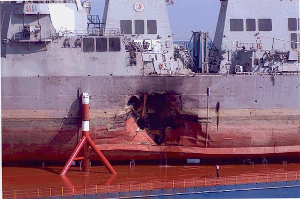 The damaged USS Cole is shown with a 45-foot hole in its ...
