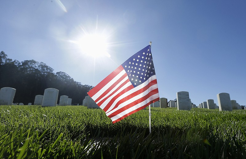 An American flag sits in front of gravestones on Veterans Day at San Francisc...