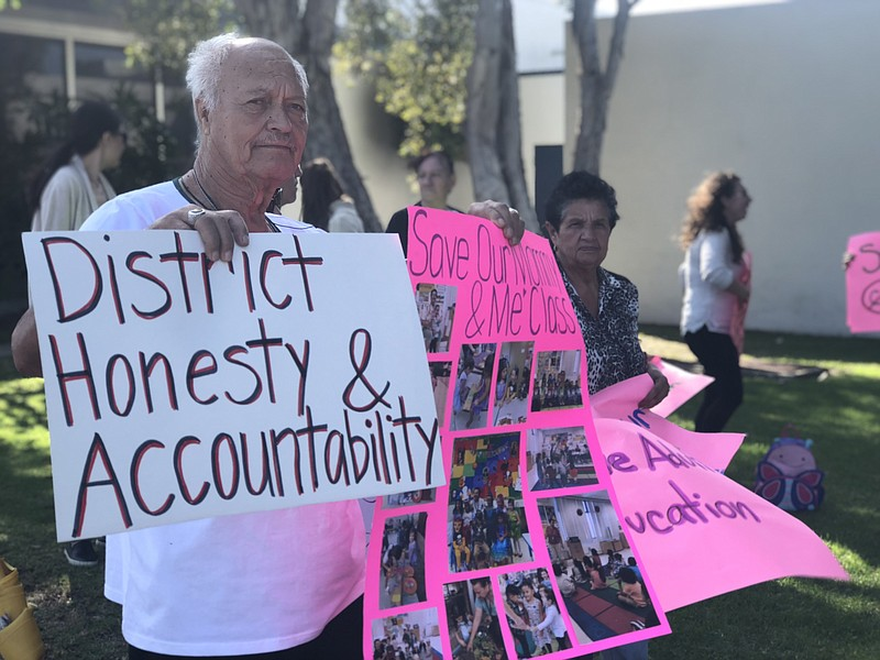 Roberto Bermudez holds a sign that reads,