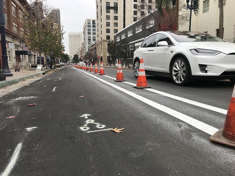 A car drives by orange traffic cones lining a future protected bike lane on J...