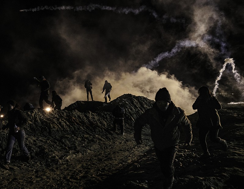 Migrants run as tear gas is thrown by U.S. Border Protection officers to the ...