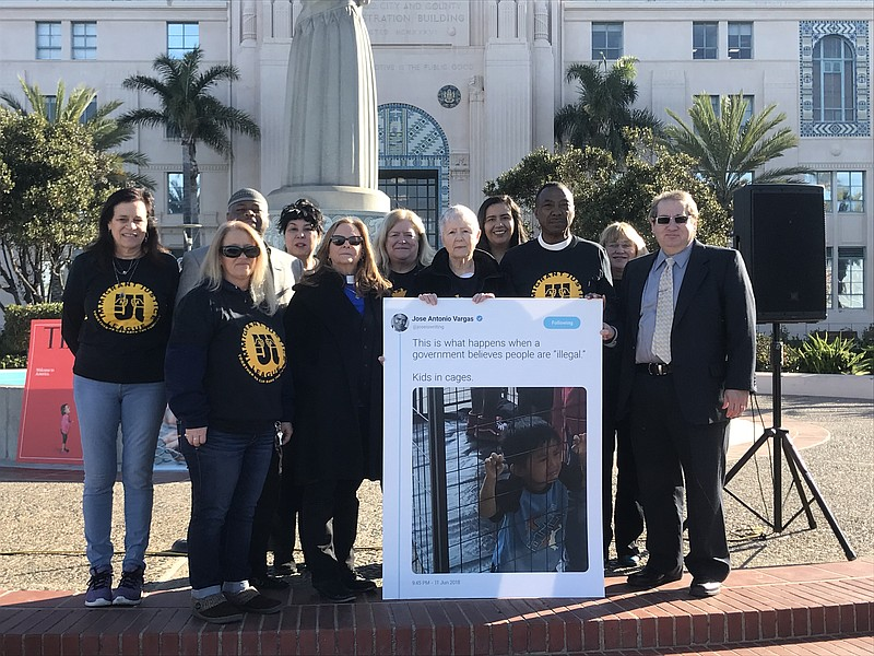 Advocates with Immigration Justice League stand outside of the San Diego Coun...