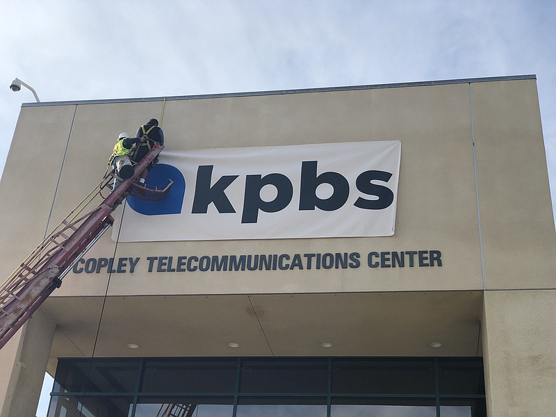 A worker places a banner of the new KPBS logo above the entrance to the KPBS ...