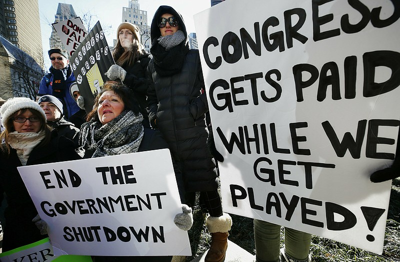 Government workers and their supporters hold signs during a protest in Boston...