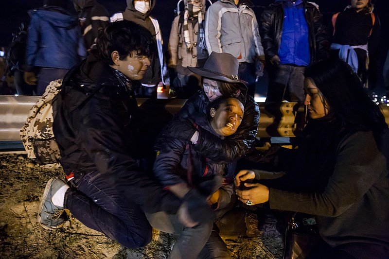 American activists comfort a migrant mother during a tear gas incident at the...