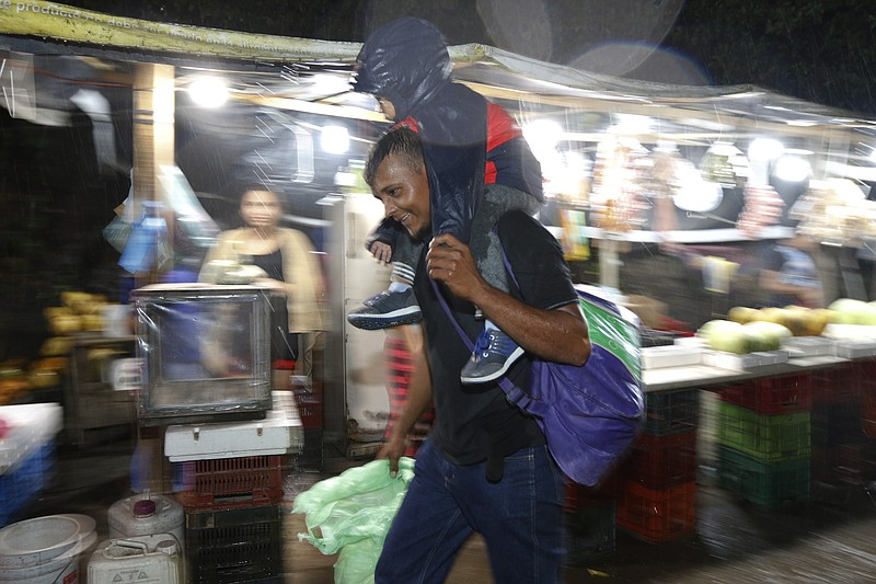 A man carries a child on his shoulders in the rain as a caravan of several hu...