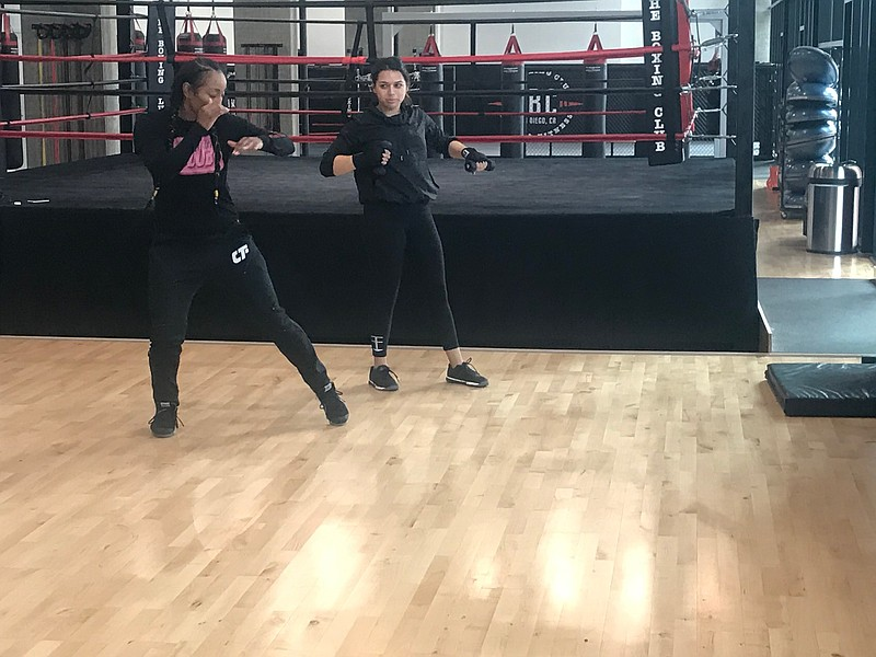 Professional boxer Raquel Miller (left) training a client at The Boxing Club ...