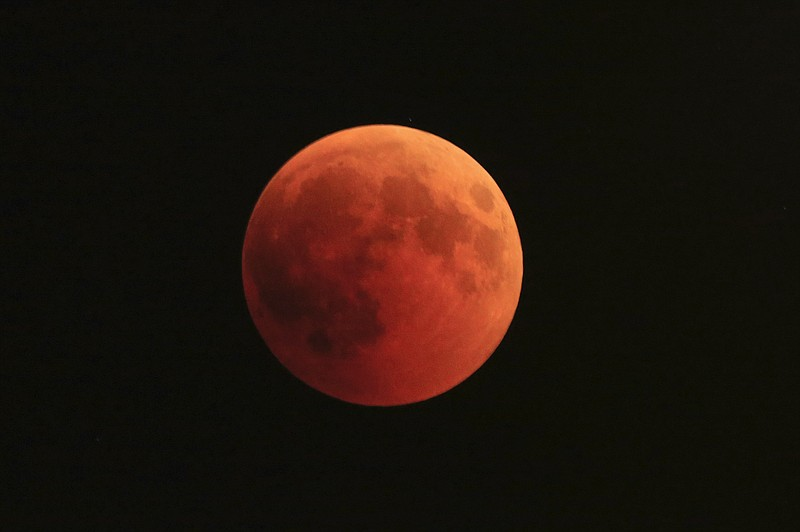 The moon turns red during a total lunar eclipse in Giv'atayim, Israel, July 2...