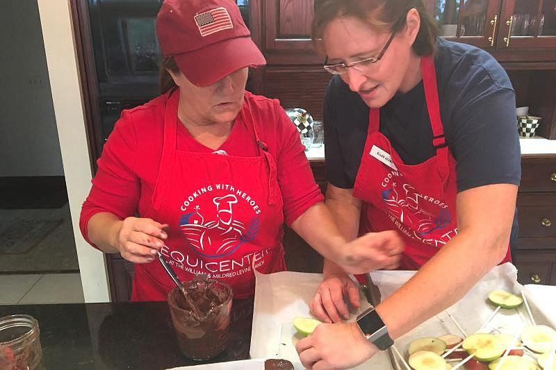 An Air Force veteran helps another veteran Linda Costello coat apples in choc...