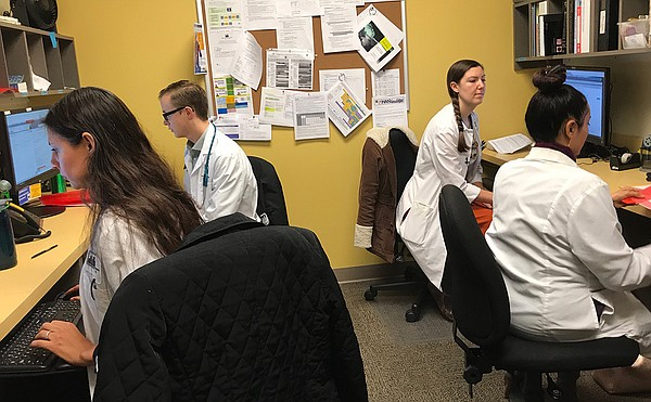Medical residents log patient information during a traini...