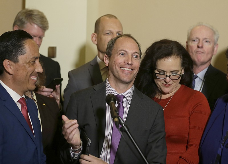 Assemblyman Brian Maienschein, center, smiles at a news conference where he a...