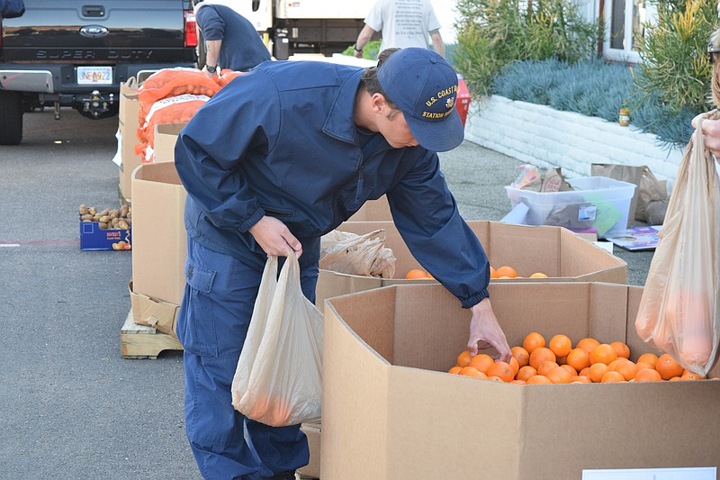 A U.S. Coast Guard service member reaches into a large box of oranges at a Fe...