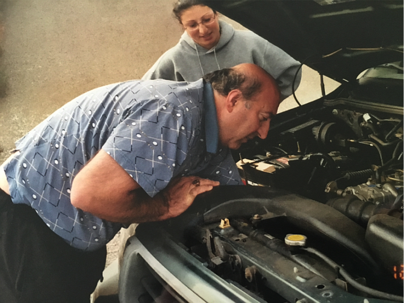Edward Agababian inspects a car engine in this undated photo.