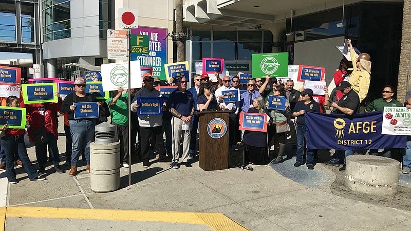 Federal workers and their unions protest the government shutdown outside of t...