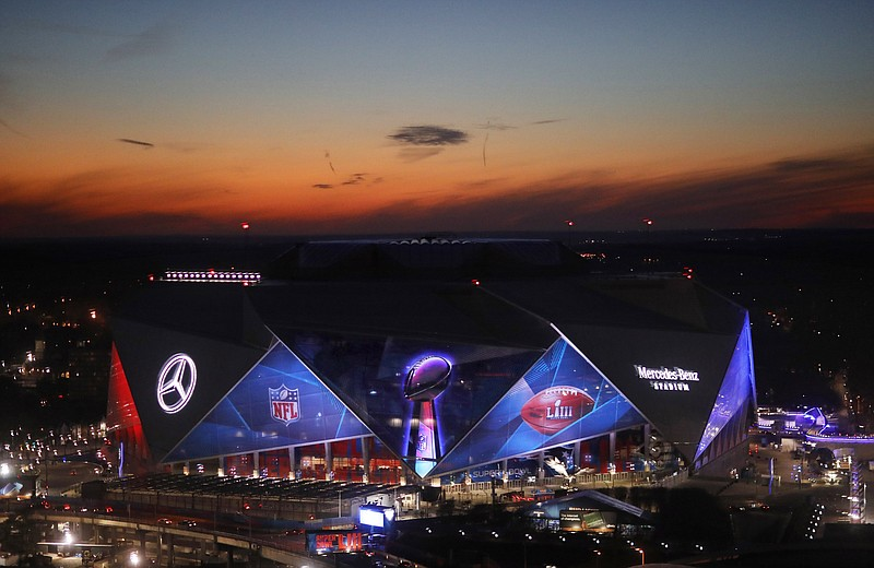 The sun sets behind Mercedes-Benz Stadium ahead of Sunday's NFL Super Bowl 53...