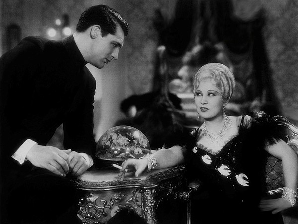 A very young Cary Grant enjoys the company of Mae West in...
