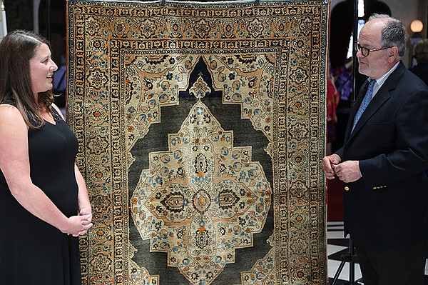 Peter Pap (right) appraises a Persian Tabriz rug, ca 1910...