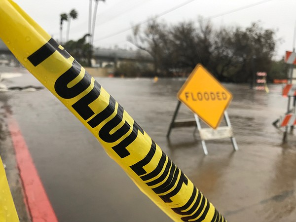 Traffic signs placed on flooded roads in Mission Valley d...
